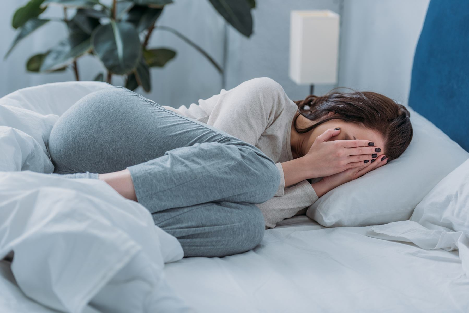 woman lying in bed anxious