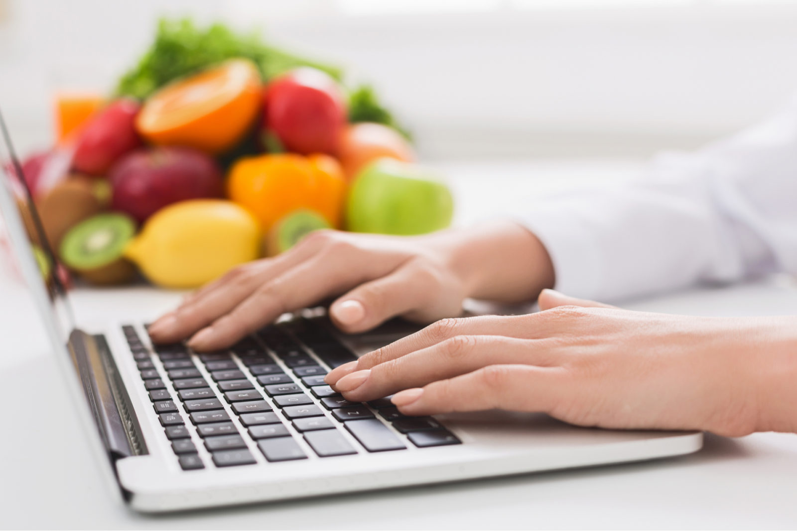 male working on laptop with healthy food behind him